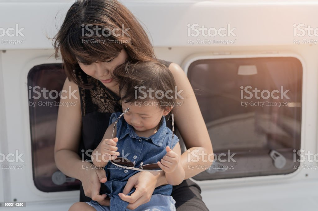 Cute baby girl and beautiful mother enjoying on luxury yacth background. zbiór zdjęć royalty-free