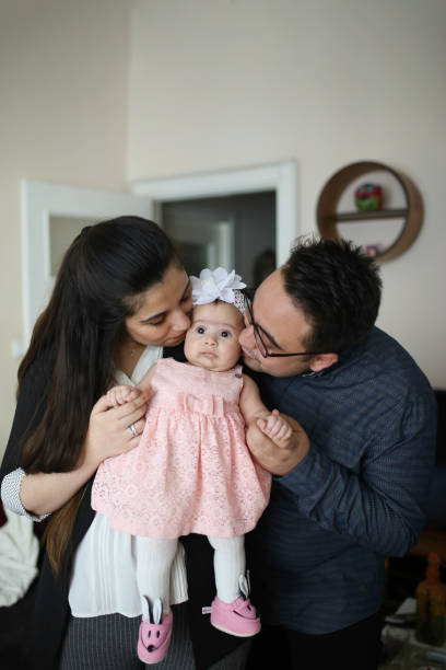 Cute baby girl being kissed by both their parents at the same time Cute baby girl being kissed by both their parents at the same time. turkish family little girl kissing dad on cheek stock pictures, royalty-free photos & images