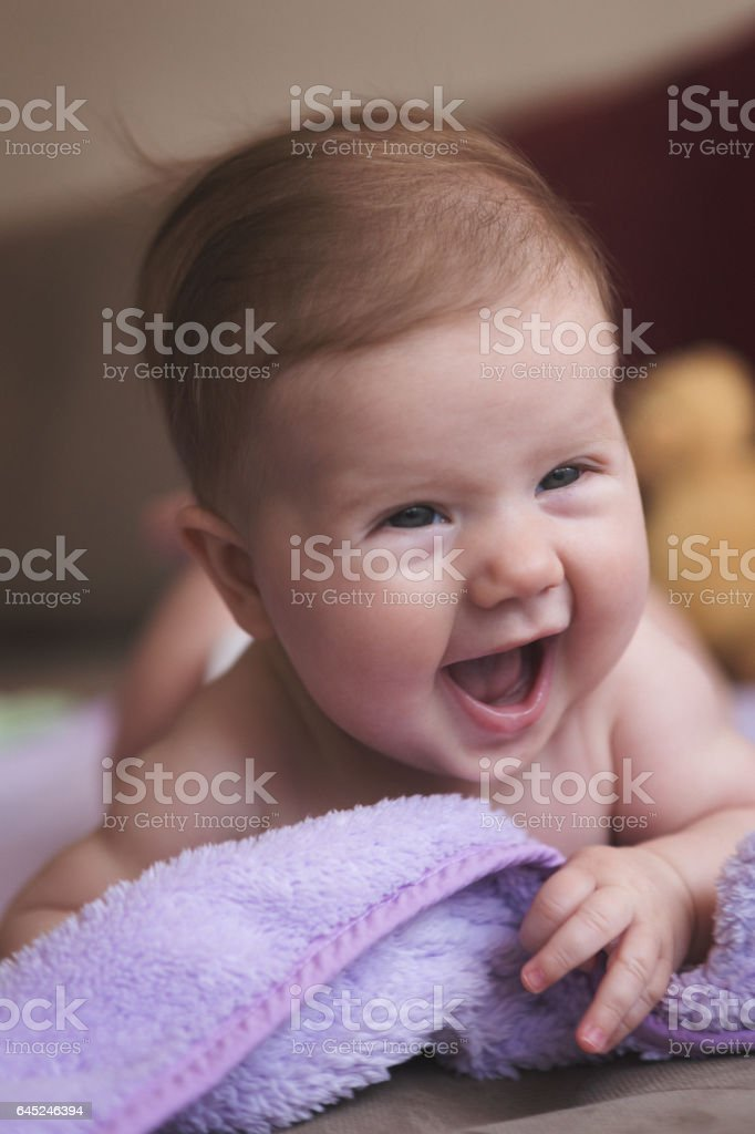 Cute baby girl crawling and smiling stock photo