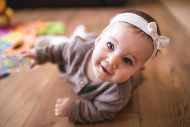 cute baby girl crawling in living room - cute stock pictures, royalty-free photos & images