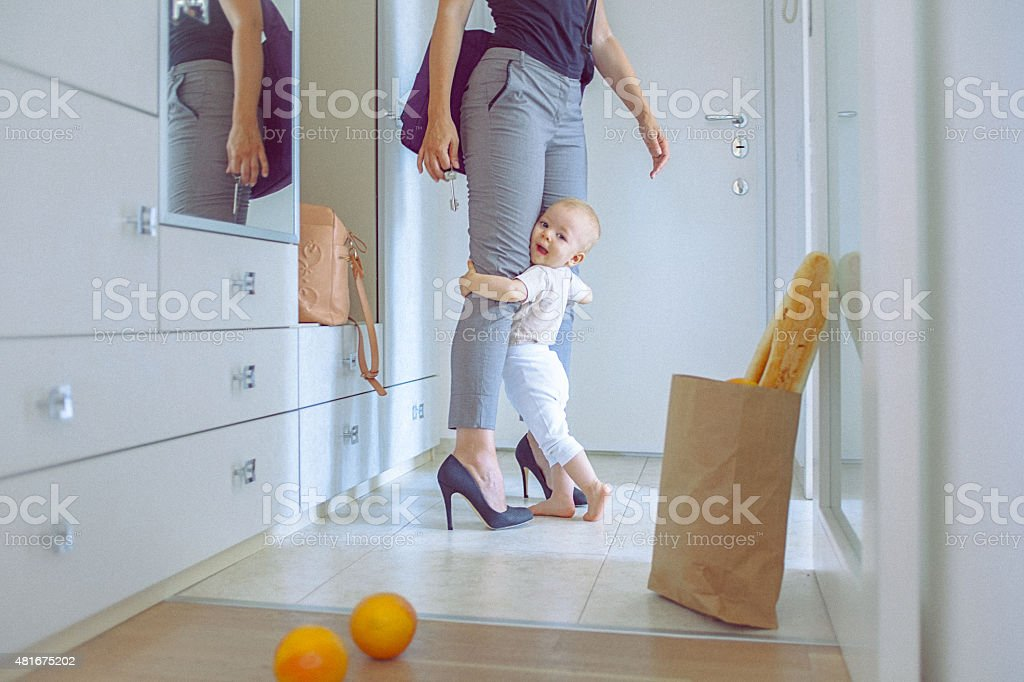 Cute baby girl cuddle with her mom hugging her legs stock photo