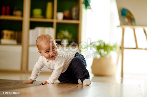 Front view of cute playful baby girl having fun on the floor while being chased by someone.