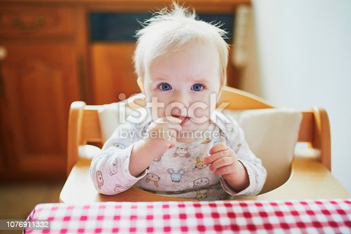 istock Cute baby girl feeding herself with finger food in the kitchen 1076911332