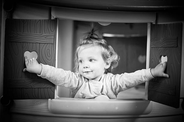 Cute baby girl head out of plastic window stock photo