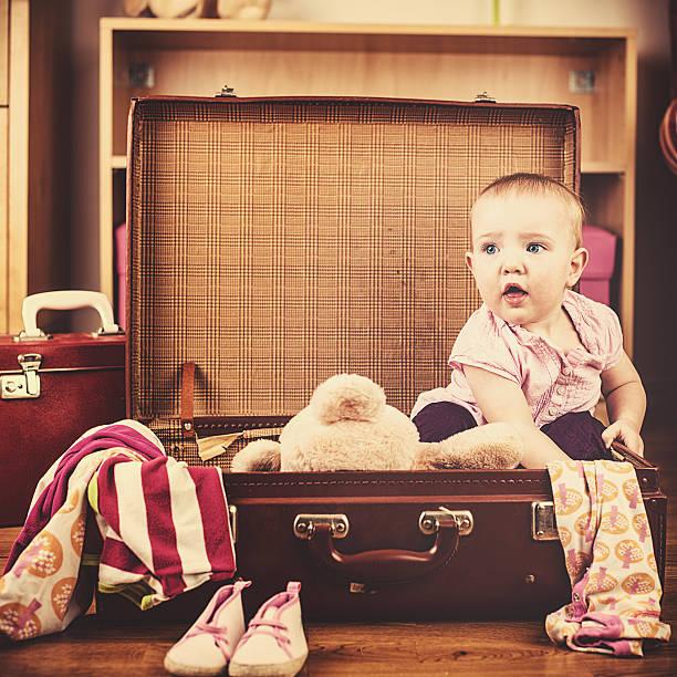 süßes baby girl in ihrem vintage koffer voller - kleinkind busy bags stock-fotos und bilder