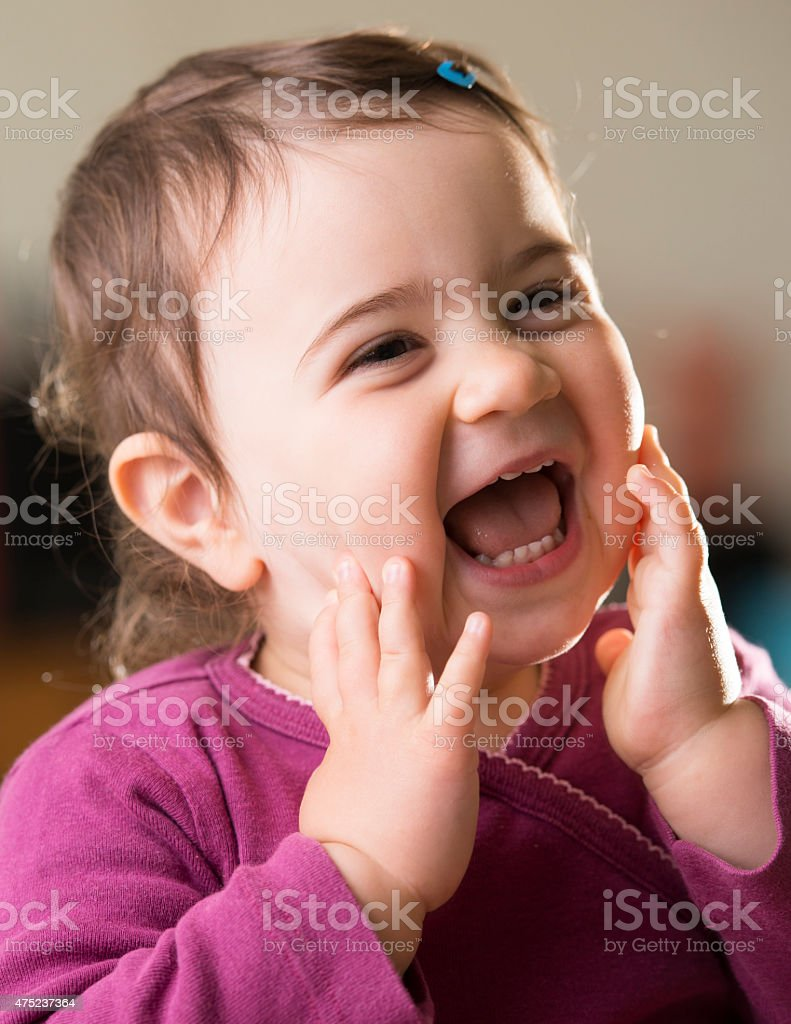 cute baby girl in purple looking aside laughing stock photo & more