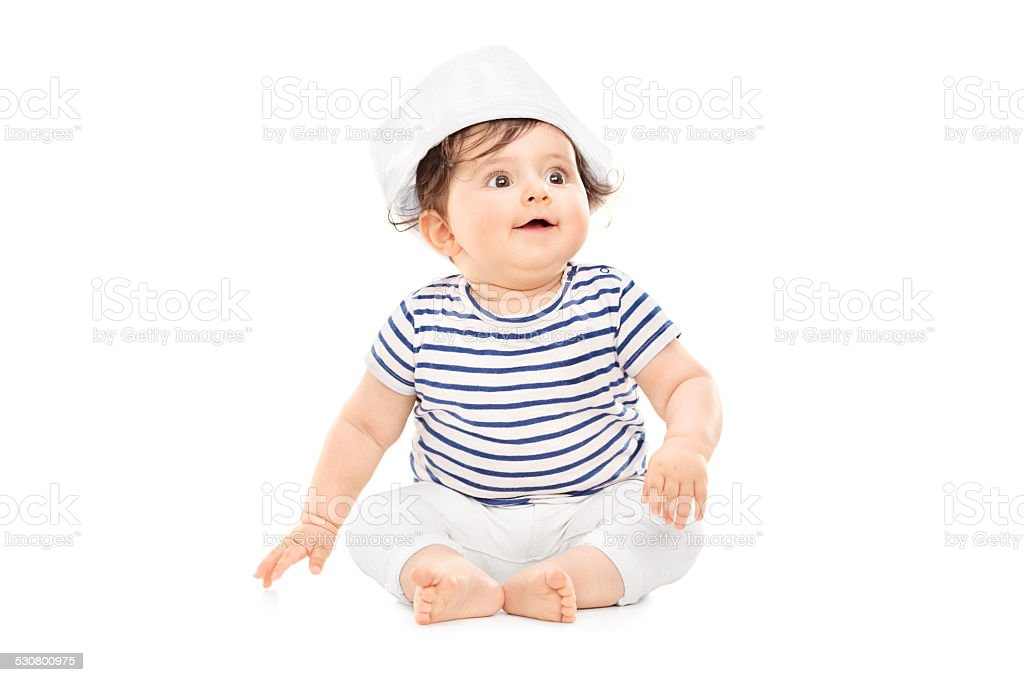 Cute baby girl in sailor outfit sitting on the floor stock photo