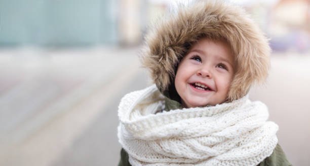 Cute baby girl in winter jacket and scarf looking up stock photo