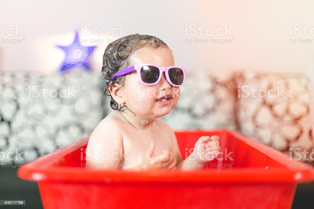 cute baby girl  is having a bath wearing sunglasses stock photo