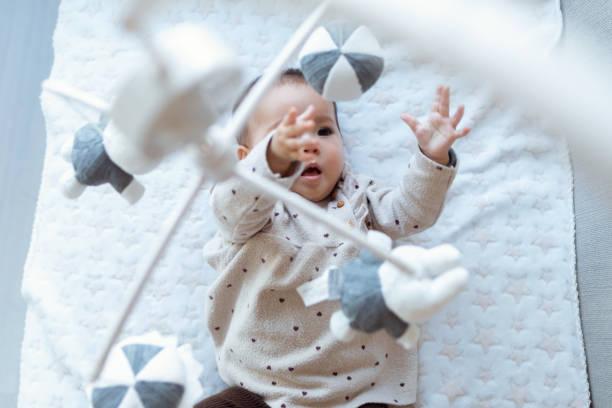 uma menina bonita está assistindo e brincando com o brinquedo móvel musical das crianças em casa. - mobile - fotografias e filmes do acervo
