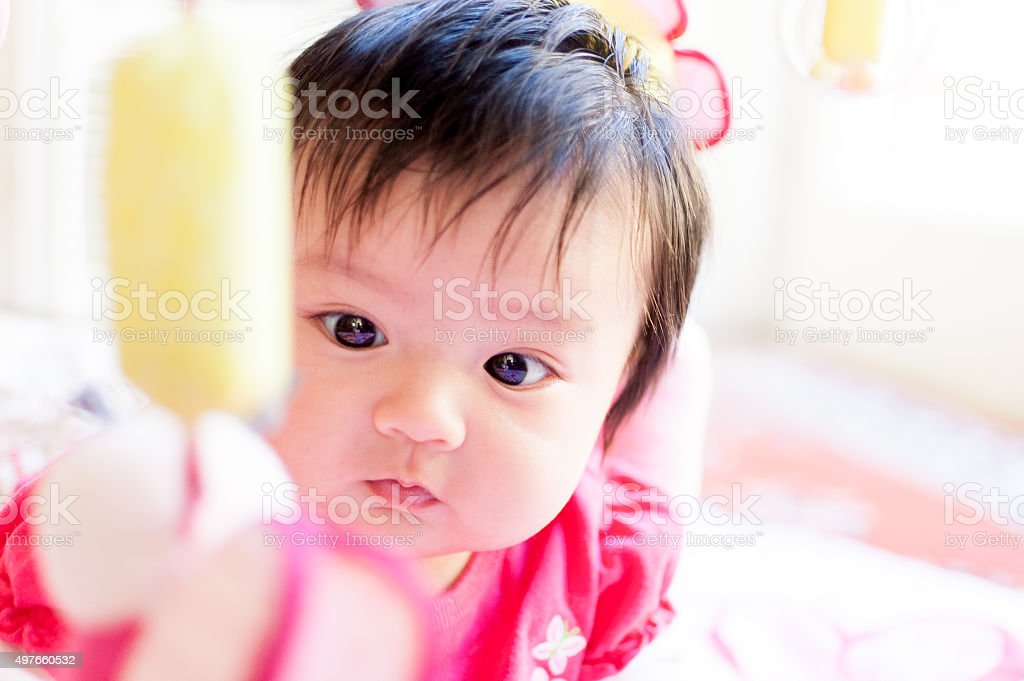 Cute baby girl looking at hanging mobile toy stock photo
