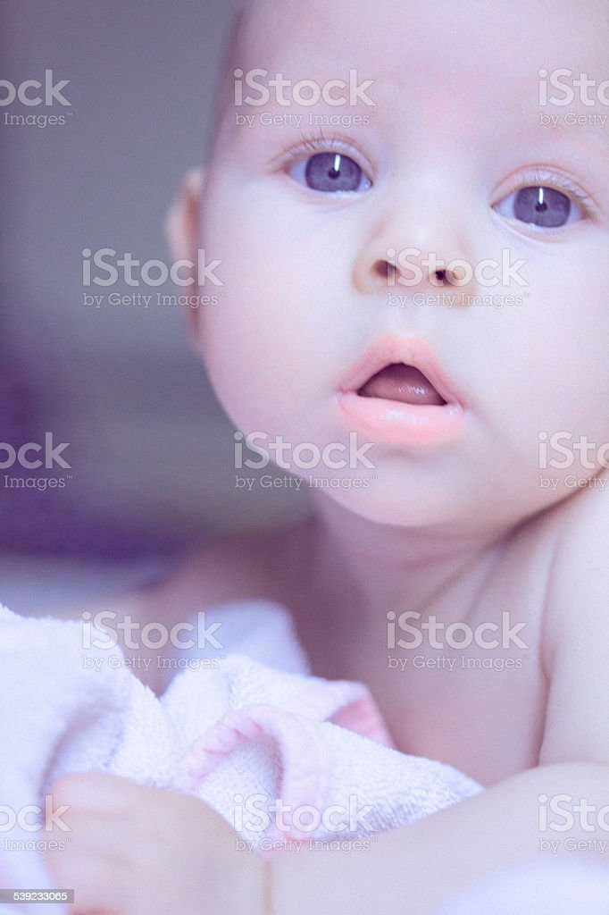 Cute baby girl lying at her stomach looking sleepy royalty-free stock photo