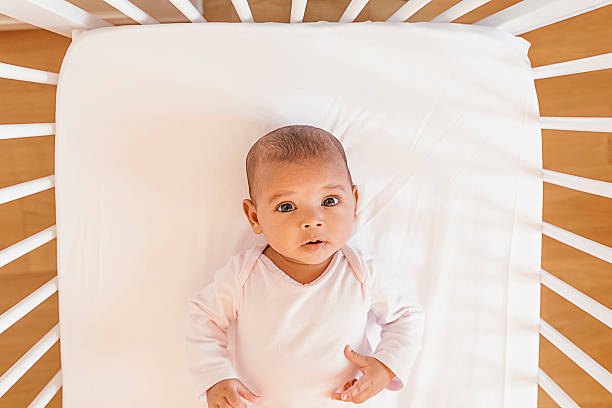 Cute Baby Girl Lying in the Crib stock photo