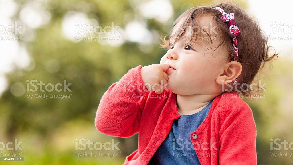 Cute baby girl outdoors on the grass stock photo