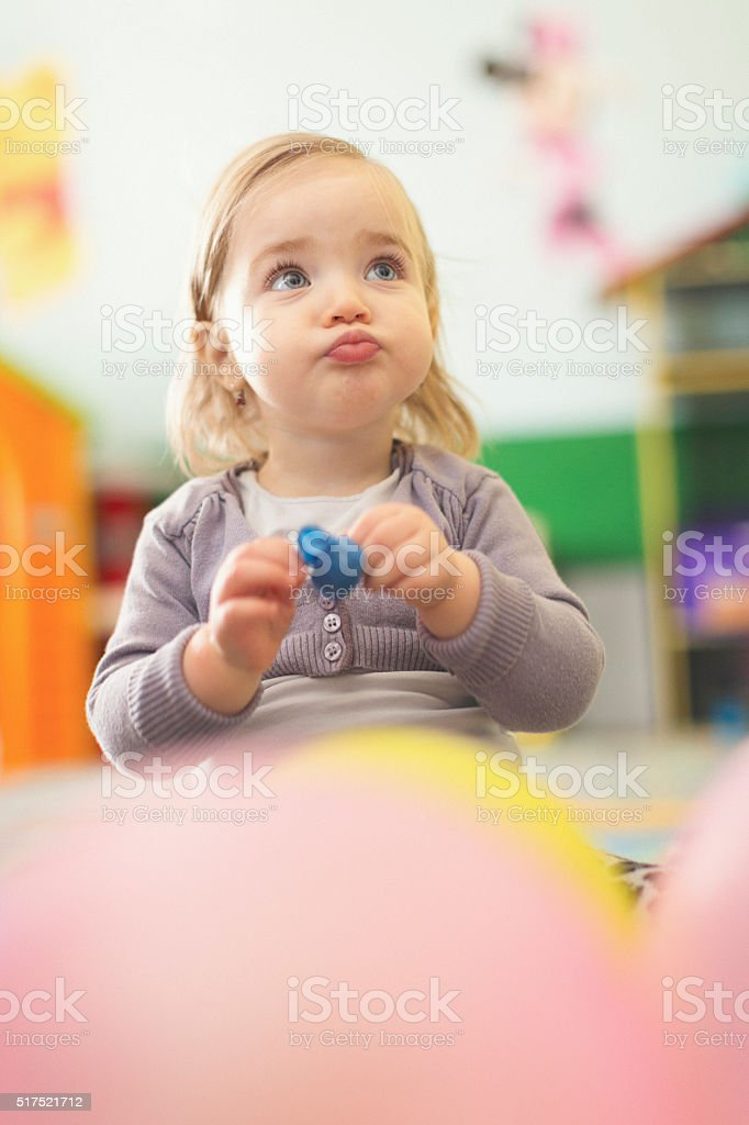 Cute baby girl playing and making a funny face stock photo