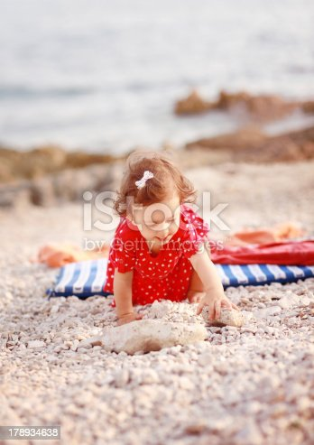 147878016 istock photo cute baby girl playing at the sandy beach 178934638