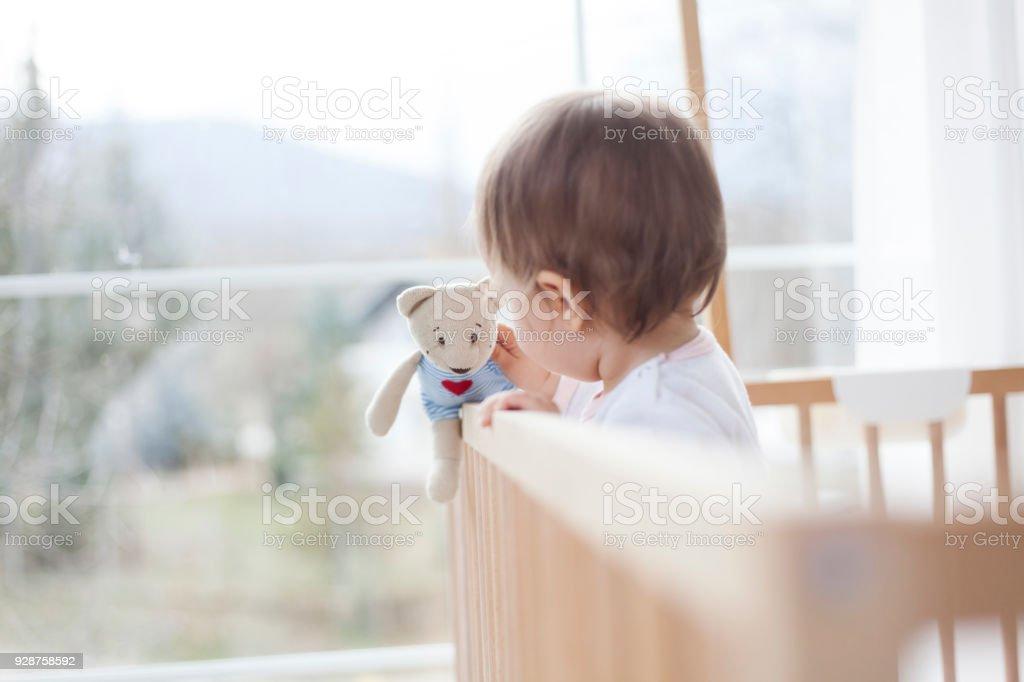 cute baby girl playing in baby crib stock photo