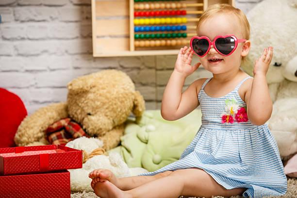 cute baby girl playing in her room - sonnenbrille kleinkind stock-fotos und bilder