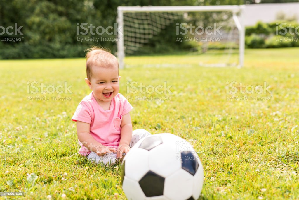 cute baby girl playing on grass with ball stock photo
