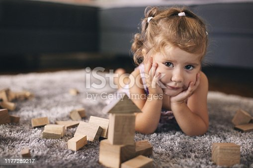 Cute baby girl playing with wooden blocks. Shallow DOF. Developed from RAW; retouched with special care and attention; Small amount of grain added for best final impression.16 bit Adobe RGB color profile.
