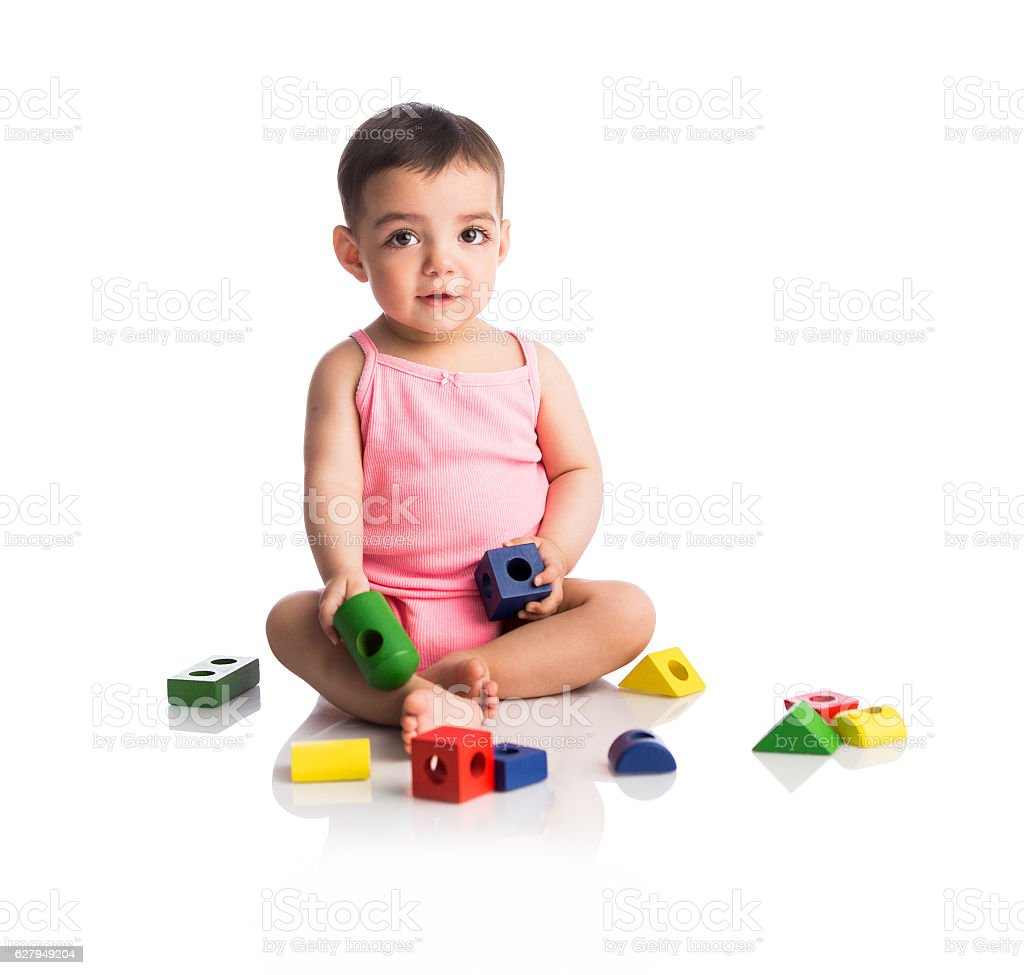 Cute baby girl sitting and playing with toys stock photo