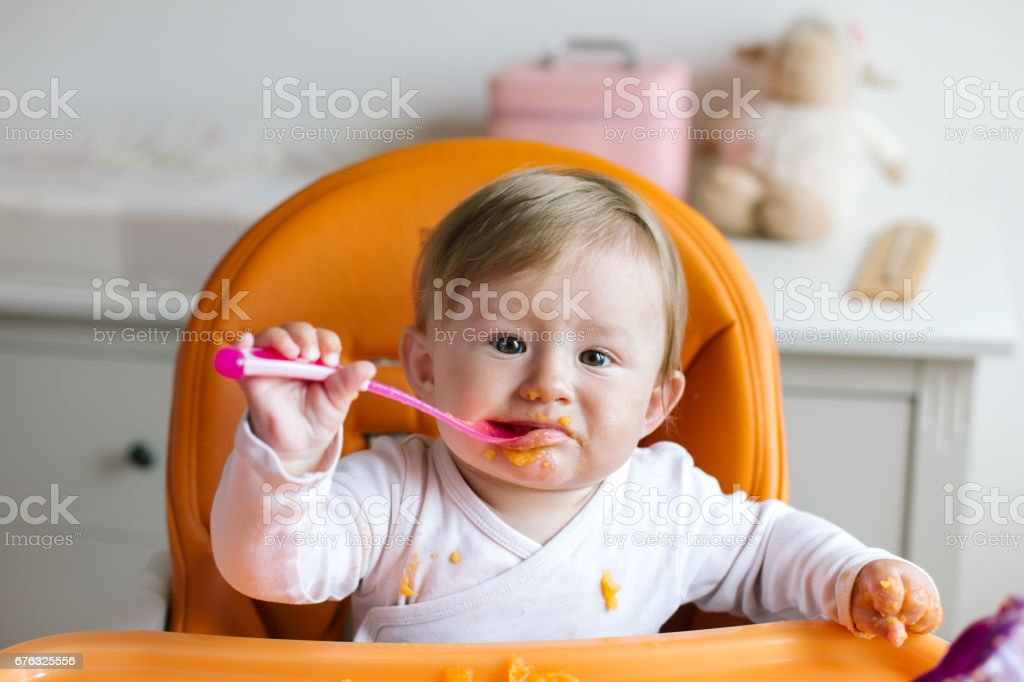 cute baby girl sitting in high chair stock photo
