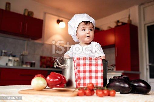 istock cute baby girl sitting inside pot 1043497522