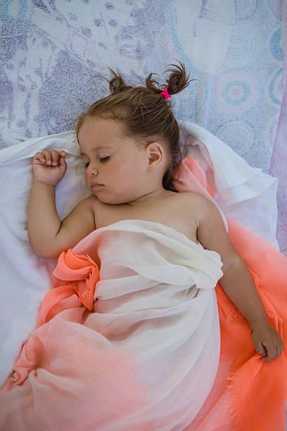 cute baby girl sleeping on the beach - küstenfamilienzimmer stock-fotos und bilder