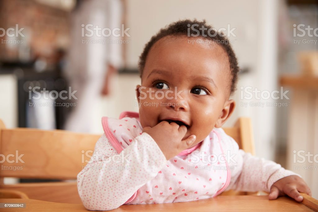 Cute Baby Girl Wearing Bib Sitting In High Chair stock photo