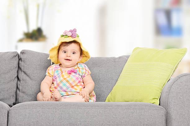 süßes baby-mädchen mit einem modischen hut sitzt auf sofa - kindermütze häkeln stock-fotos und bilder