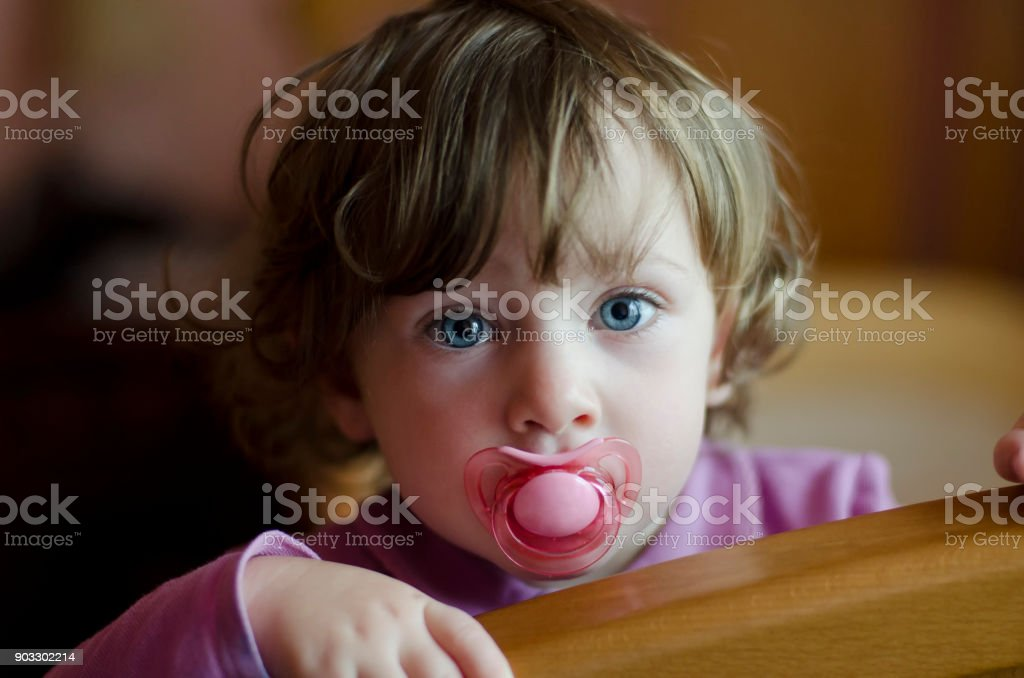 cute baby girl with a soother in her mouth stock photo