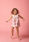 Cute baby girl with barefoot jumping on pink background.