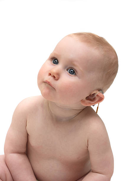 Cute baby girl with hearing aid stock photo