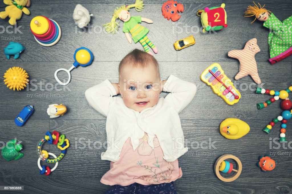 cute baby girl with lot of toys on the floor. top view royalty-free stock photo