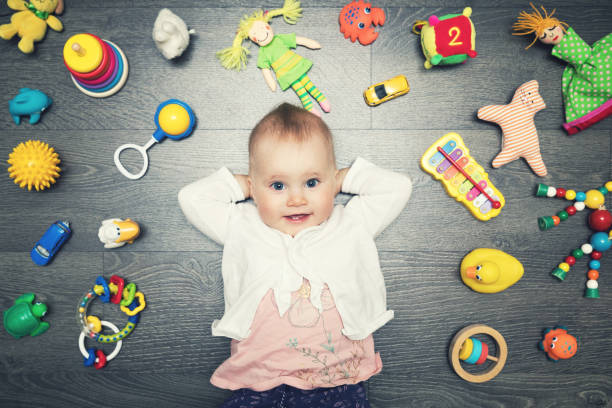 cute baby girl with lot of toys on the floor. top view stock photo