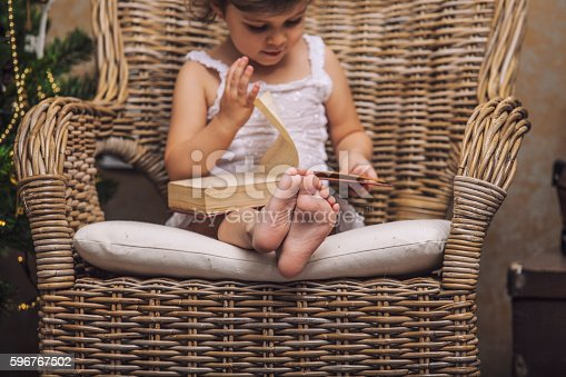 istock Cute baby in a chair reading a book in interior 596767502