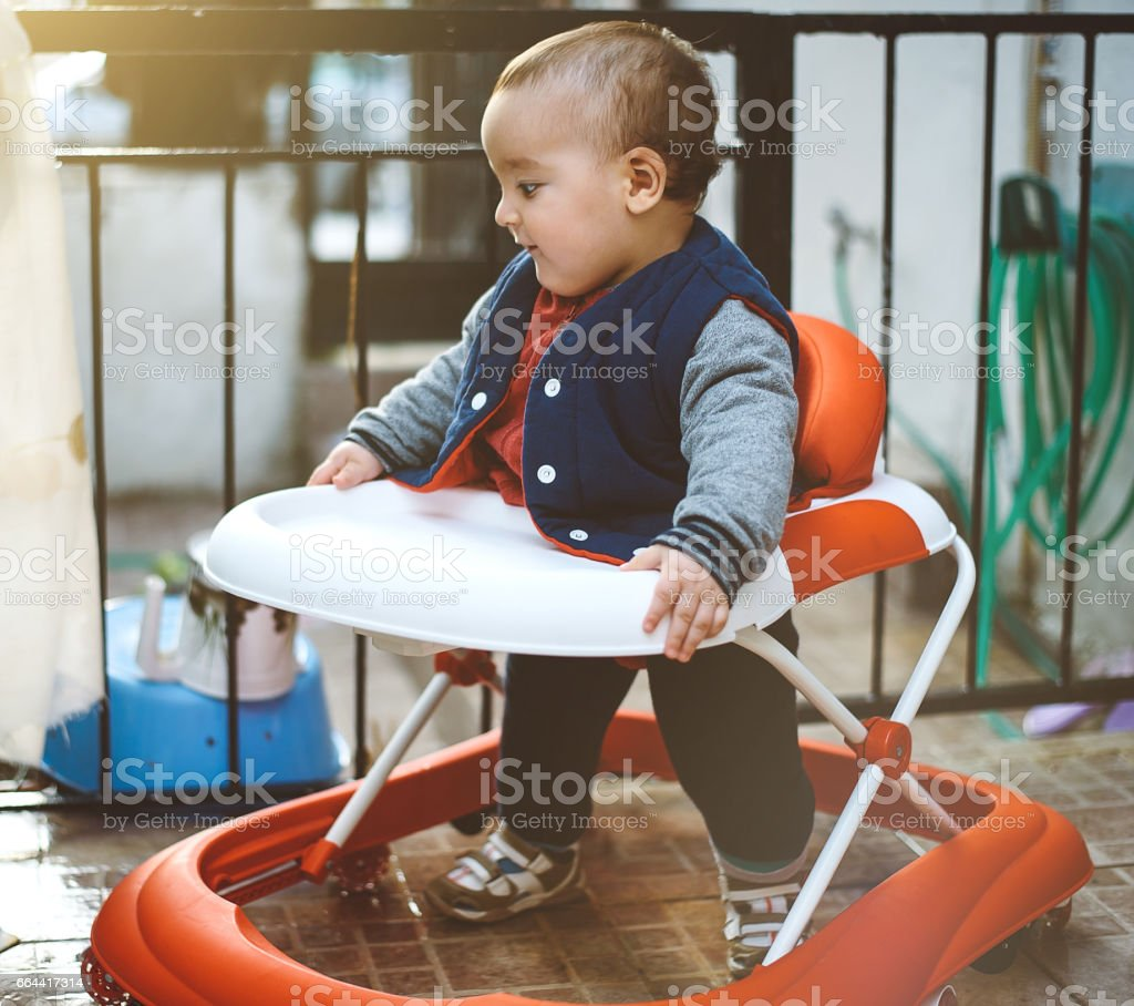 Cute baby in baby walker stock photo
