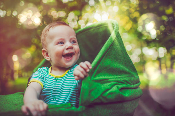 Cute baby in carriage outdoors in summer stock photo
