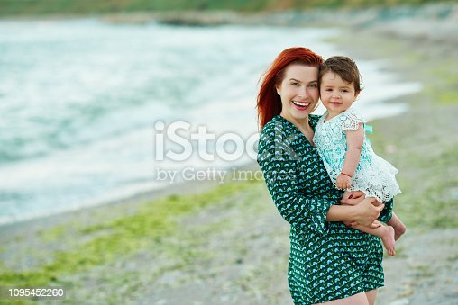 604367022 istock photo cute baby in the arms on her mother on the beach 1095452260