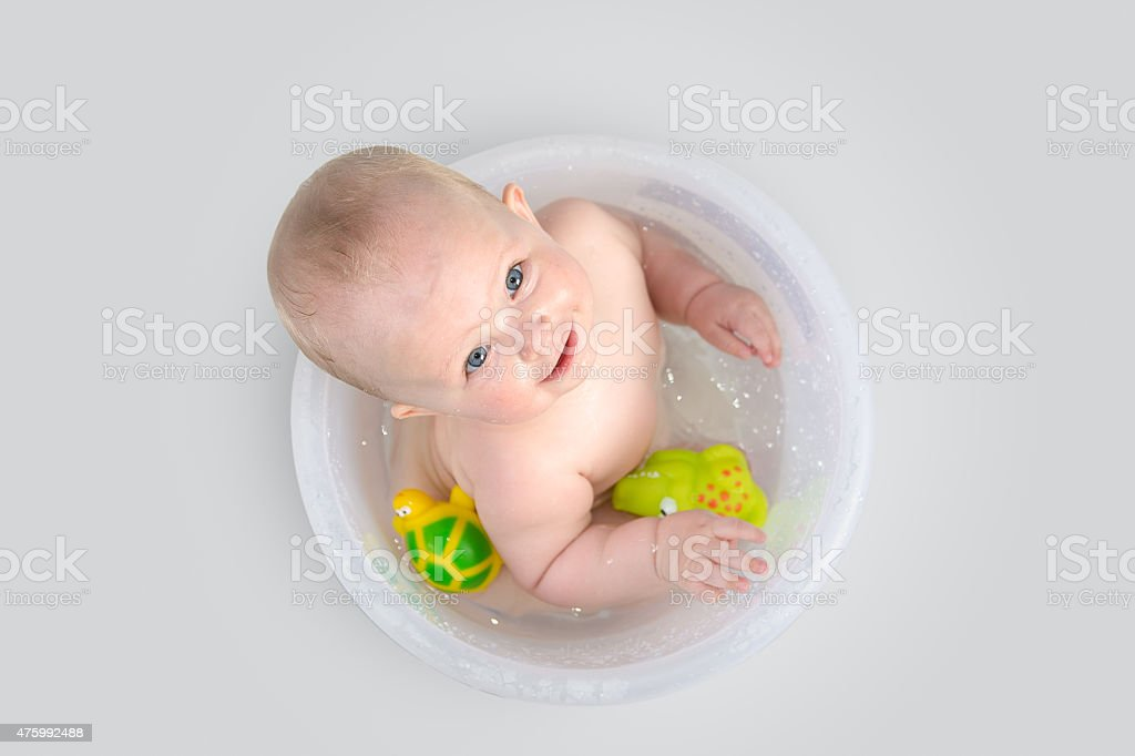 Cute baby in transparent bucket and playing with toys stock photo