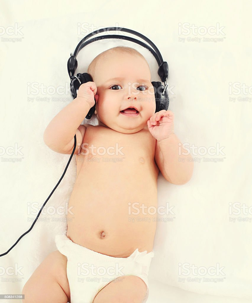 Cute baby listens to music in headphones lying on bed stock photo