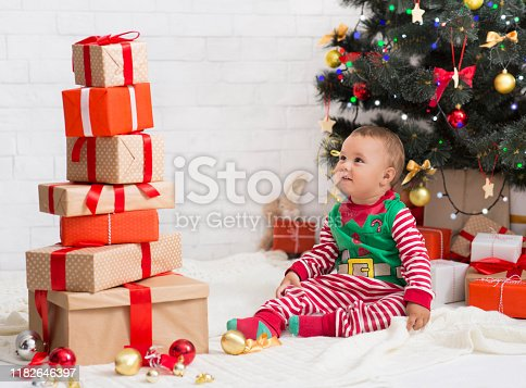 No Christmas gifts. Unhappy baby elf with empty present box sitting near Xmas tree, free space