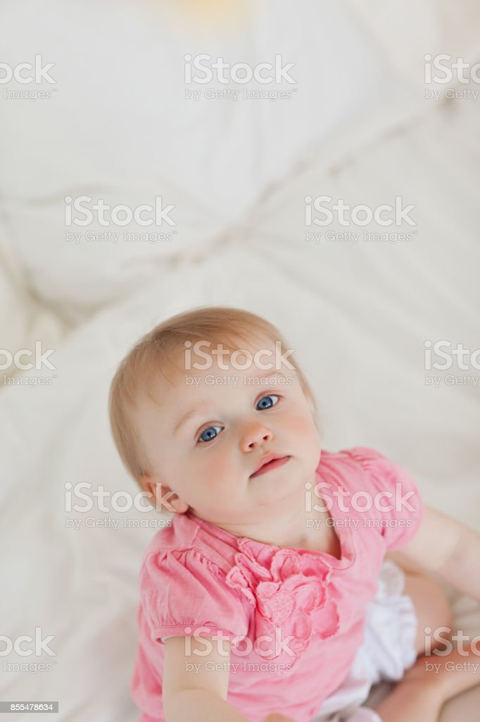 Cute baby looking at the camera while sitting on a bed stock photo