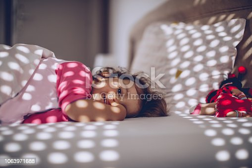 1008826222istockphoto Cute baby lying in bed 1063971688