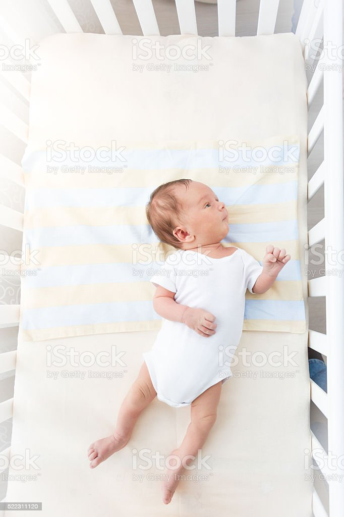 Cute baby lying in white cradle at sunny day stock photo