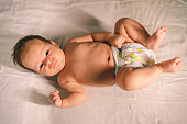 Cute baby in diaper lying on bed at home