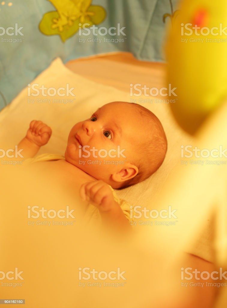 Cute baby lying on bed stock photo