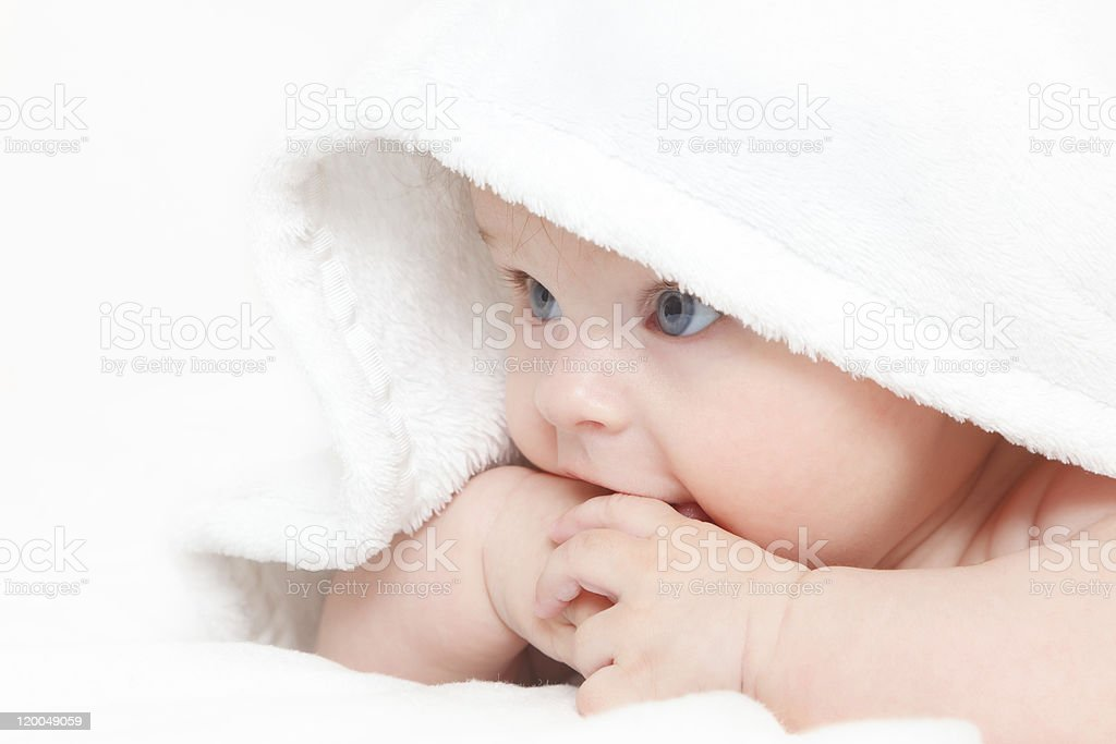 Cute baby peeking out from under a white blanket royalty-free stock photo