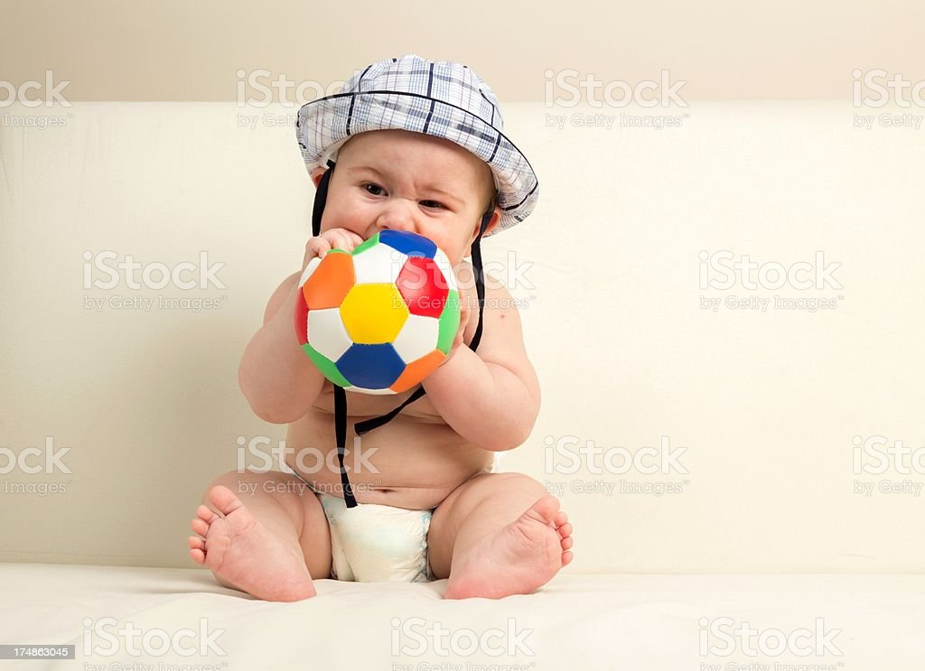 Cute baby playing ball biting royalty-free stock photo