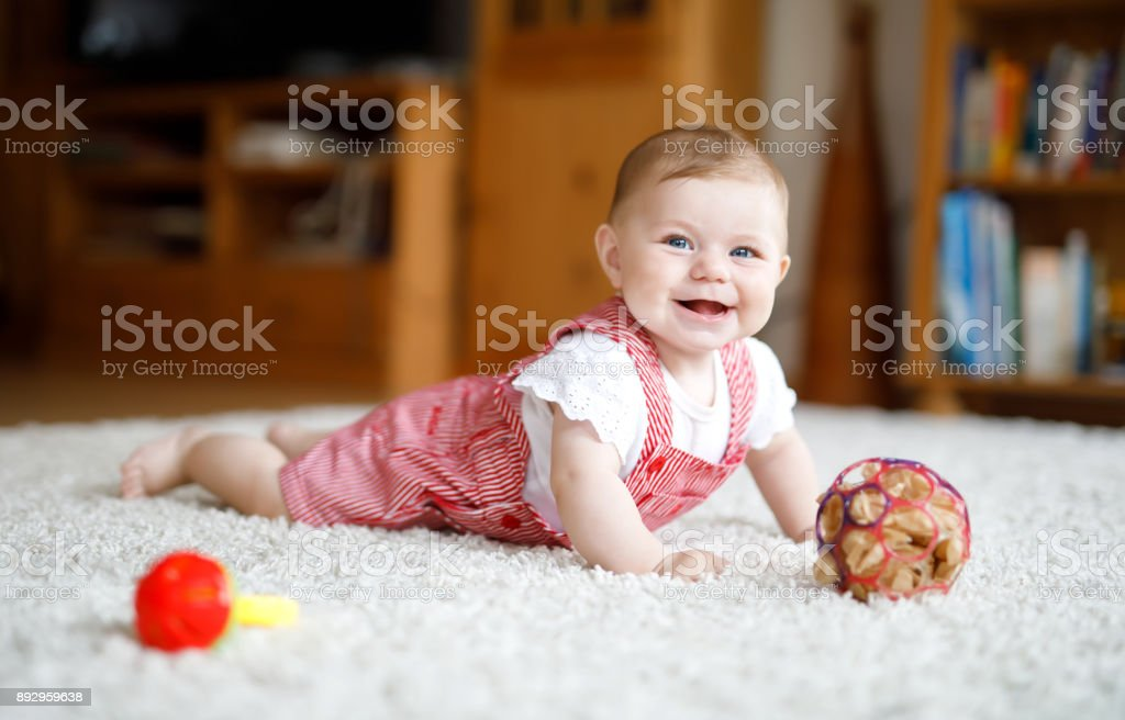 Cute baby playing with colorful rattle education toy. Little girl looking at the camera and crawling stock photo